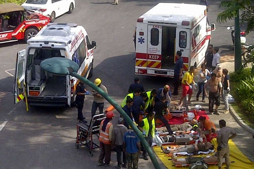 Emergency personnel attending to some of the workers injured in an accident at a worksite in Sentosa on Jan 29, 2014.