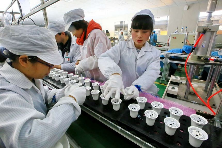 Chinese employees working on an energy-saving bulb production line at a lighting factory in Suining, south-west China's Sichuan province, on Feb 28, 2017.