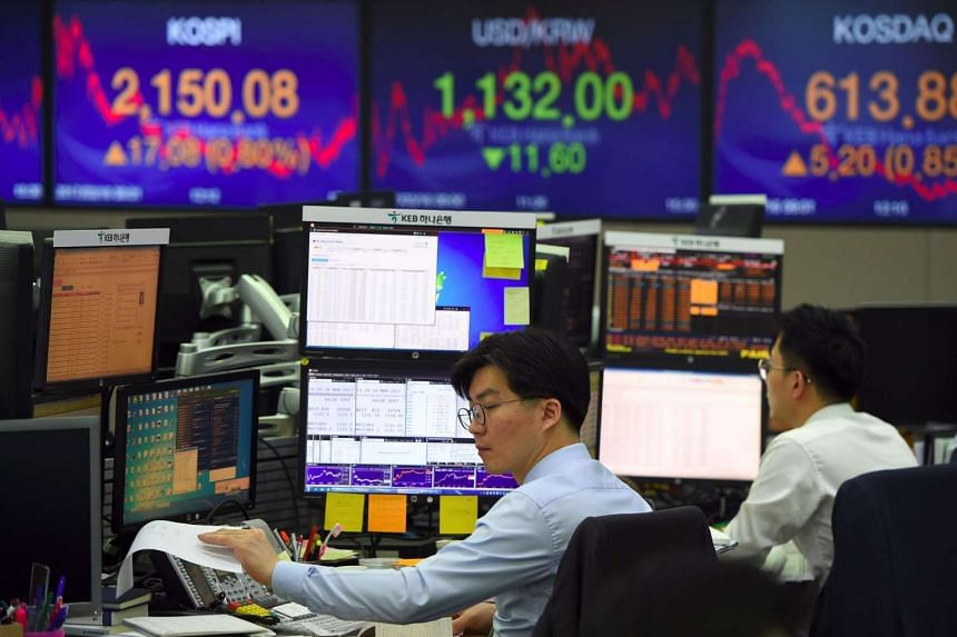 Currency dealers monitor exchange rates in a trading room at the KEB Hana Bank in Seoul, on March 16, 2017.