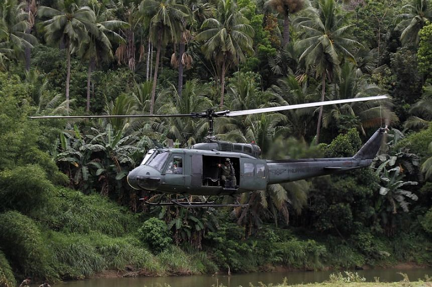 Filipino soldiers in a helicopter patrol the town of Ibanga, Bohol island, Philippines, on April 12, 2017.