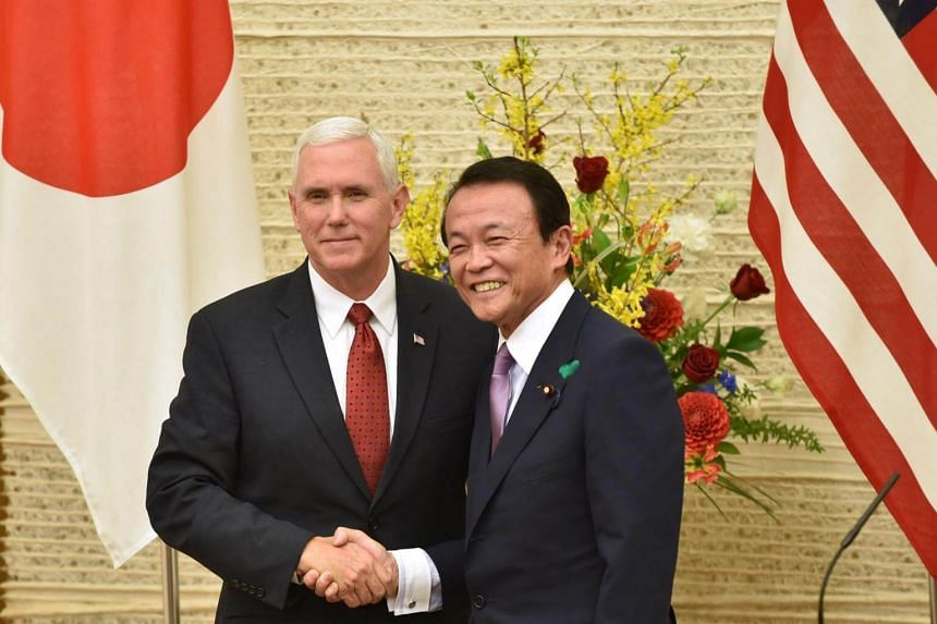 US Vice-President Mike Pence (left) shaking hands with Japanese Finance Minister Taro Aso during a press conference in Tokyo on April 18, 2017.