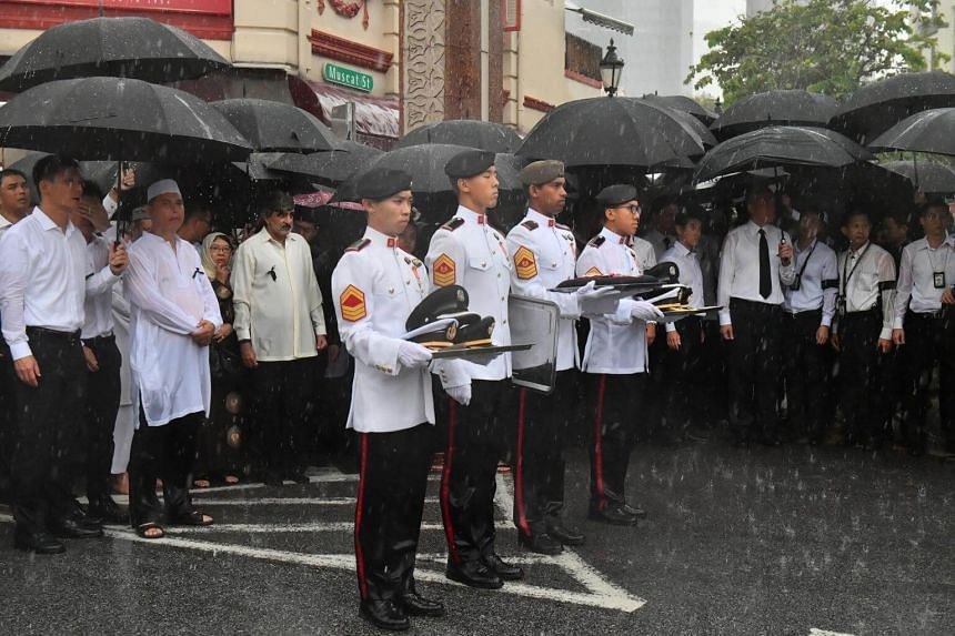 People, including Prime Minister Lee Hsien Loong, watching the State Flag-draped casket being loaded onto the gun carriage outside Sultan Mosque on April 18, 2017.