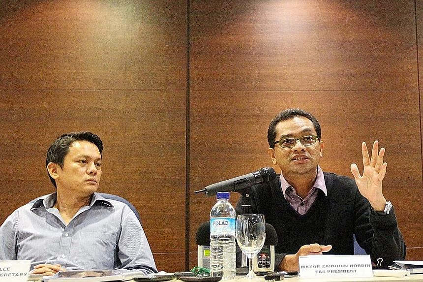 FAS general secretary Winston Lee looking on as then president Zainudin Nordin spoke at a media conference back in January 2011. Game Changers have listed eight questions for Lee to answer.
