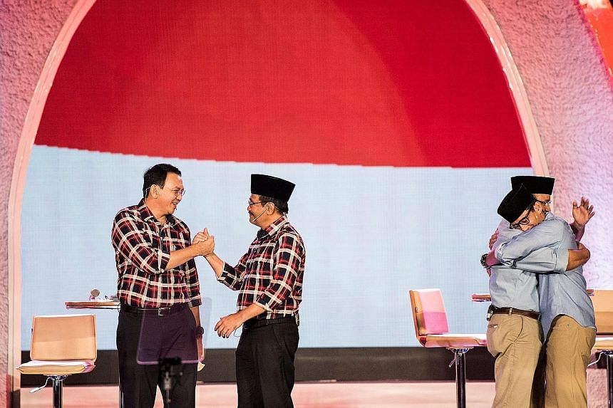 From left: Incumbent Jakarta governor Basuki Tjahaja Purnama shaking the hand of his deputy, Mr Djarot Saiful Hidayat, as rival candidate for the gubernatorial election Anies Baswedan hugs his running mate, Mr Sandiaga Uno, at a televised debate last