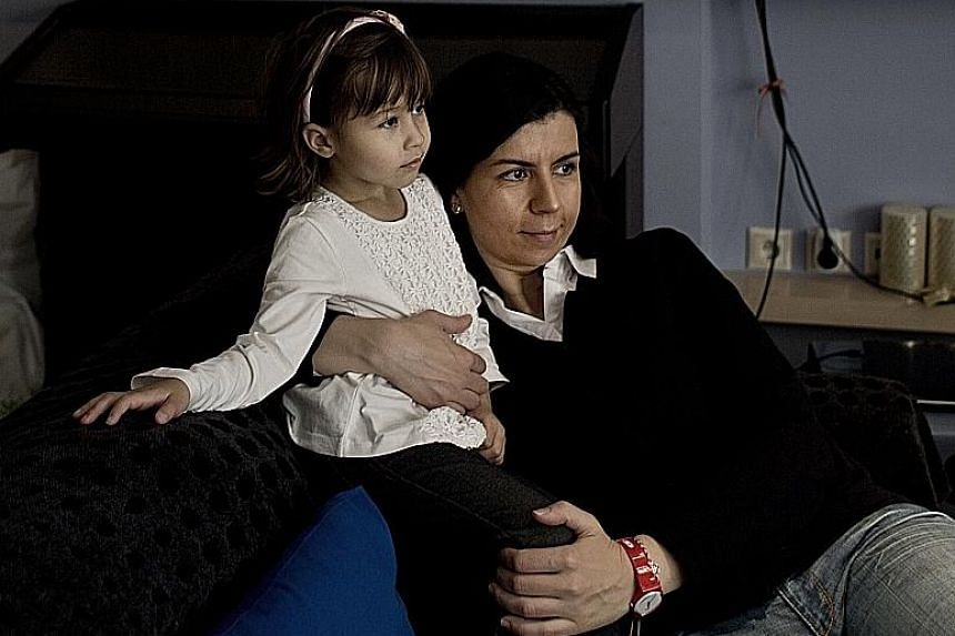 Ms Maria Karaklioumi in her Athens apartment with her four-year-old niece Georgia. The pollster has decided against having children for fear that she will not be able to offer them a stable future