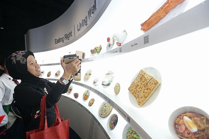 Junyuan Primary vice-principal Hafsah Abdullah checking out her choice of food in an interactive exhibit at the revamped Kidney Discovery Centre of the National Kidney Foundation yesterday. The exhibit allows visitors to calculate the calories and su