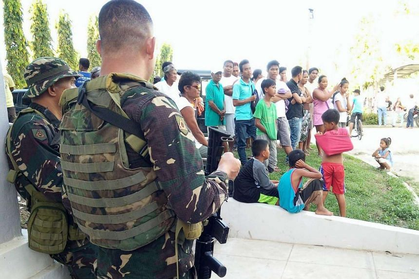 Filipino soldiers stand guard next to residents during a military operation against Abu Sayyaf in the town of Inabanga resort island of Bohol, Philippines, on April 11, 2017.