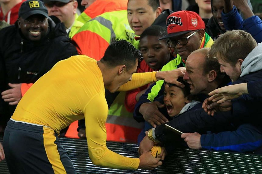 Arsenal's Chilean striker Alexis Sanchez gives his match shirt to a young fan following the match.