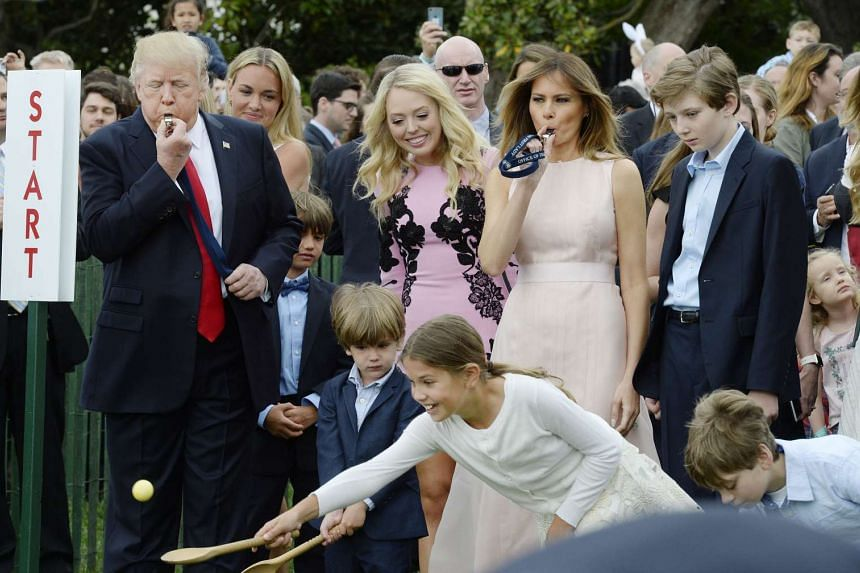 US President Donald Trump, left, and First Lady Melania, right, blow a whistle to start the annual Easter Egg Roll at  the White House on April 17, 2017.