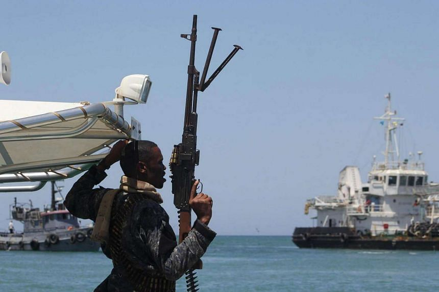 A maritime policeman on a tag-boat guards oil tanker Aris-13, which was released by pirates, as it sails to dock on the shores of the Gulf of Aden in the city of Bosasso, northern Somalia's semi-autonomous region of Puntland.