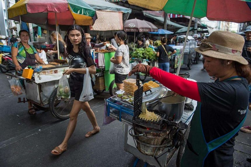 A vendor prepares a waffle on her street food cart at a local market in downtown Bangkok on Feb 22, 2017.
