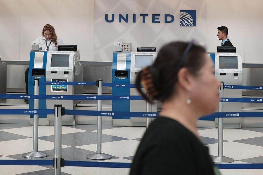 Passengers arrive for flights at the United Airlines terminal at O'Hare International Airport, on April 12, 2017.