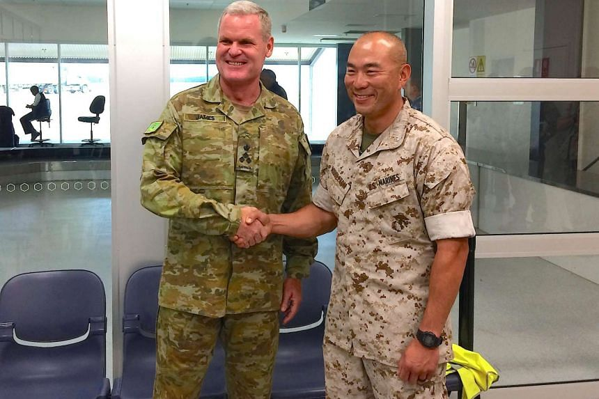 Lieutenant Colonel Brian Middleton (right) shakes hands with Australian Army officer Brigadier Mick Ryan after arriving for the sixth annual Marines' deployment at Darwin, on April 18, 2017.