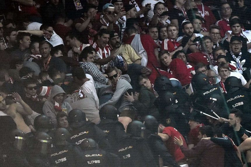 Riot police clash with Bayern Munich fans in the tribunes during the match against Real Madrid at the Santiago Bernabeu stadium in Madrid.