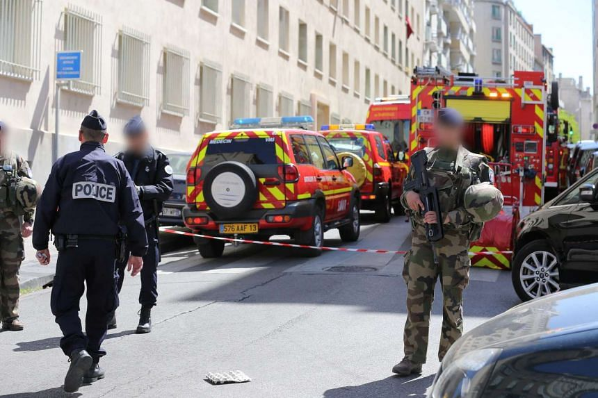 French soldiers, policemen and firefighter vehicles at the site of a police search operation at the home of one of two men arrested, in the third district of Marseille, France,  April 18, 2017.