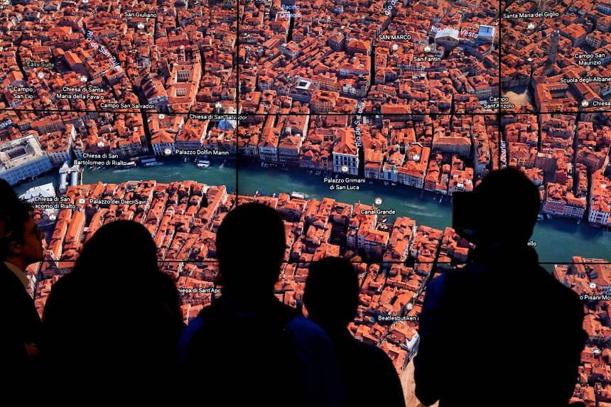 People look at a Google Earth map of Venice, Italy, as Google Earth unveils a revamped version of the application.