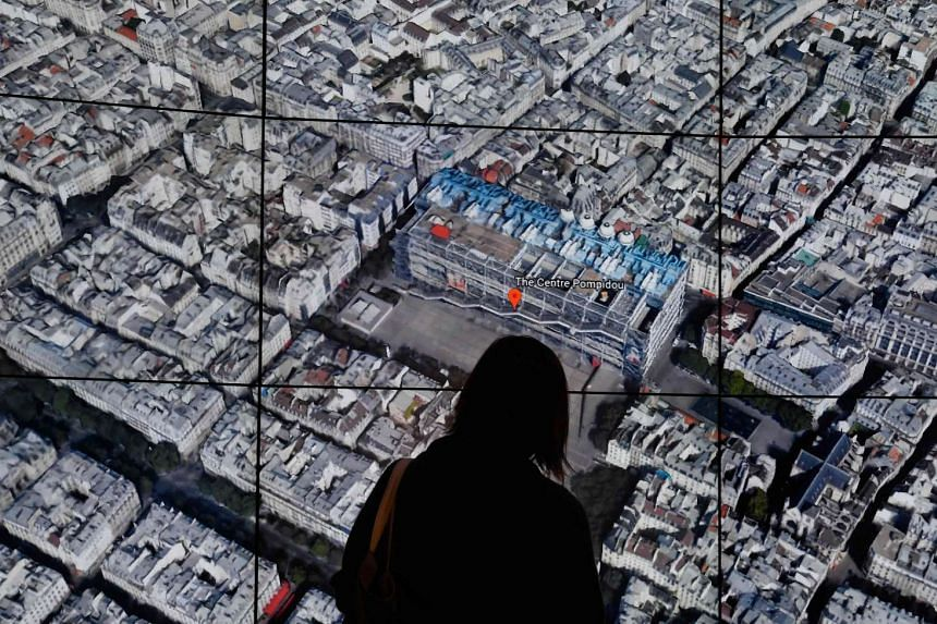 A person looks at a Google Earth map of Paris, France, as Google Earth unveils a revamped version of the application.