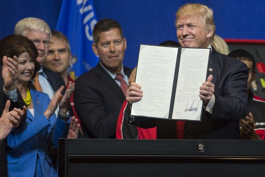 Trump holds up a Buy American, Hire American Executive Order after signing at Snap-On Tools in Kenosha, Wisconsin, April 18, 2017.