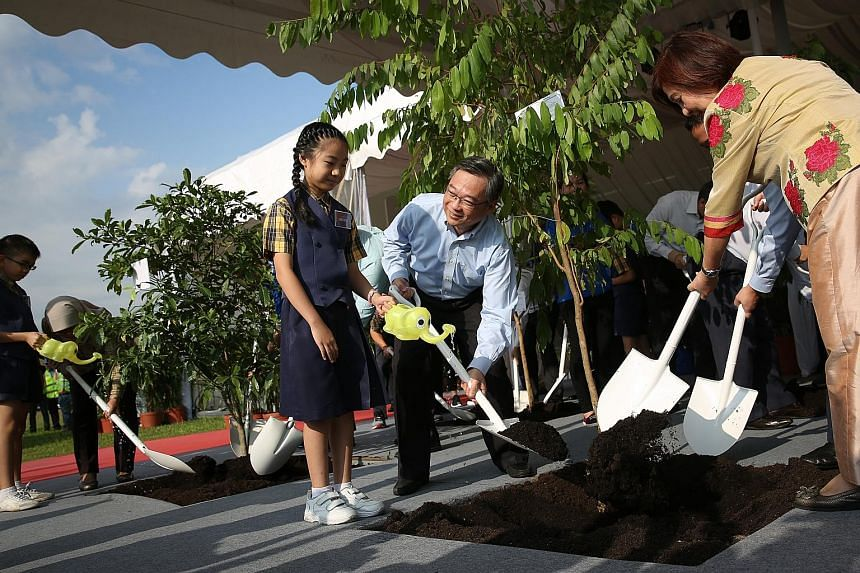 Health Minister Gan Kim Yong planting a tree with an Admiralty Primary School pupil and Alexandra Health System chairman Jennie Chua at the Woodlands Health Campus' ground-breaking ceremony yesterday.