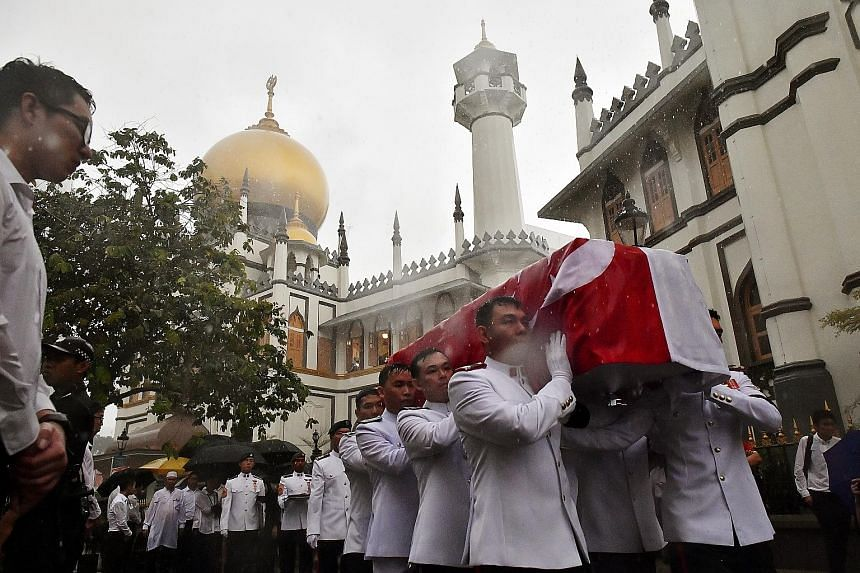 Pallbearers carrying Mr Othman Wok's coffin outside Sultan Mosque yesterday. A Singapore flag was draped over the coffin, with the crescent and stars lying over the head and close to the heart of one of the nation's founding fathers.