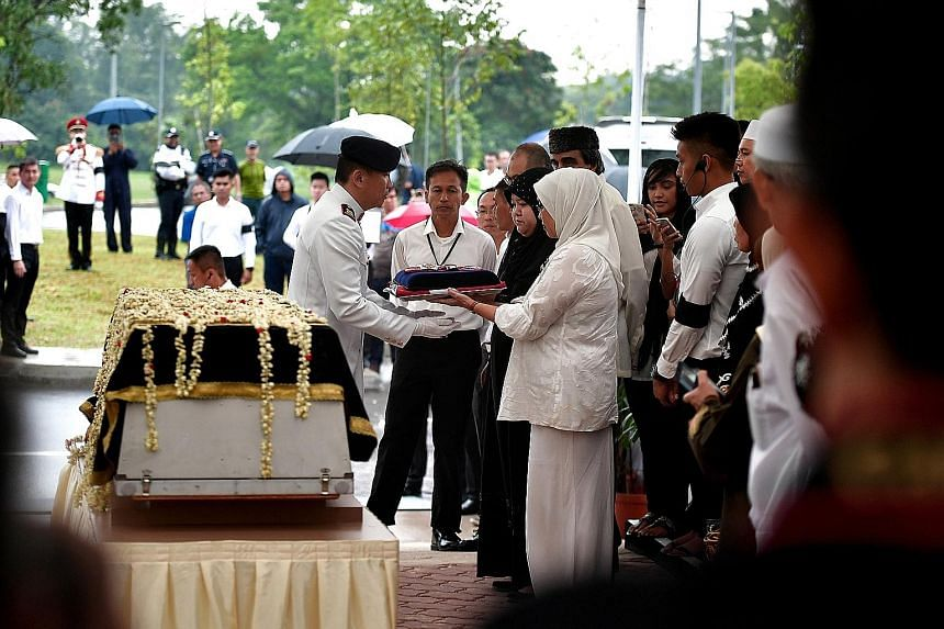 Mr Othman Wok's daughters Lily (in white) and Diana receiving the state flag from Lieutenant-Colonel Loh Chia Siong at Choa Chu Kang Cemetery yesterday. In a letter of condolence by Dr Yaacob Ibrahim to Mr Othman's widow, the minister said he believe