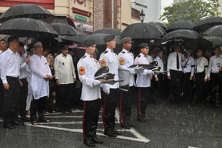Mourners, including Mr Lee Hsien Loong, watching as Mr Othman Wok's coffin was loaded onto the gun carriage at Sultan Mosque yesterday.