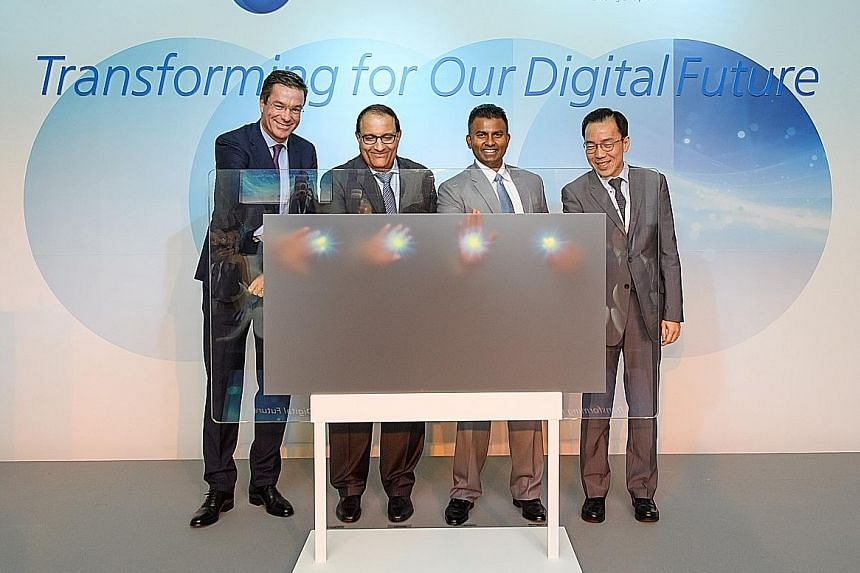 (From left) Mr Nicolas Defauw, Mr S. Iswaran, Mr Magesvaran Suranjan and Economic Development Board chairman Beh Swan Gin activating a simulated panel yesterday to symbolically launch Procter & Gamble's E-Centre in Singapore. P&G said the project rea