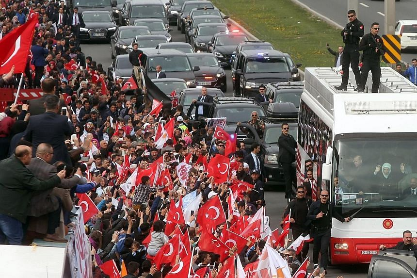 Turkish President Recep Tayyip Erdogan and his wife Emine acknowledging supporters from a bus during a parade in Ankara on Monday, following the referendum result which granted the head of state extra powers.