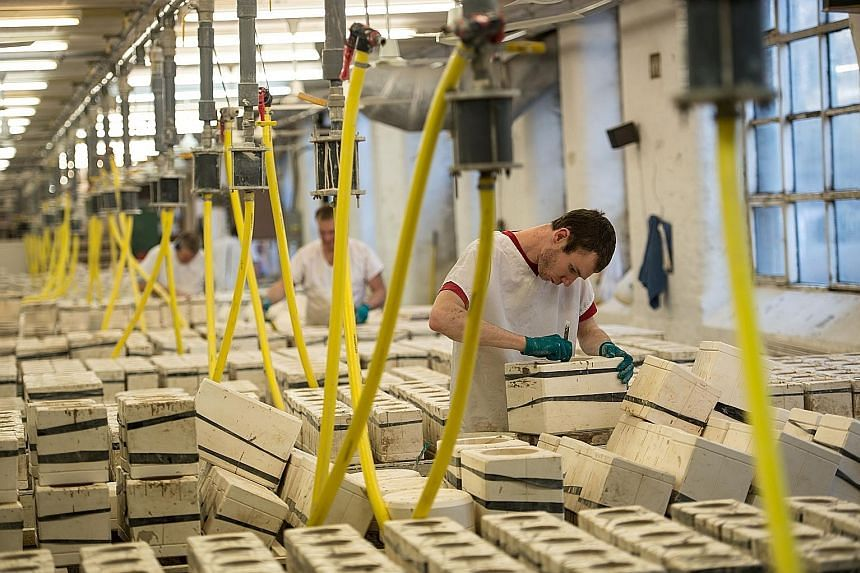 A pottery manufacturing plant in Britain. The International Monetary Fund raised its 2017 global growth forecast yesterday due to manufacturing and trade gains in Europe, Japan and China. However, it also warned that protectionist policies threaten t