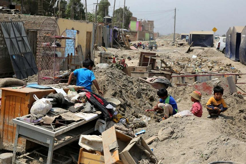 Children playing outside their home a month after torrential rains caused flooding and widespread destruction in Carapongo, Lima, Peru.