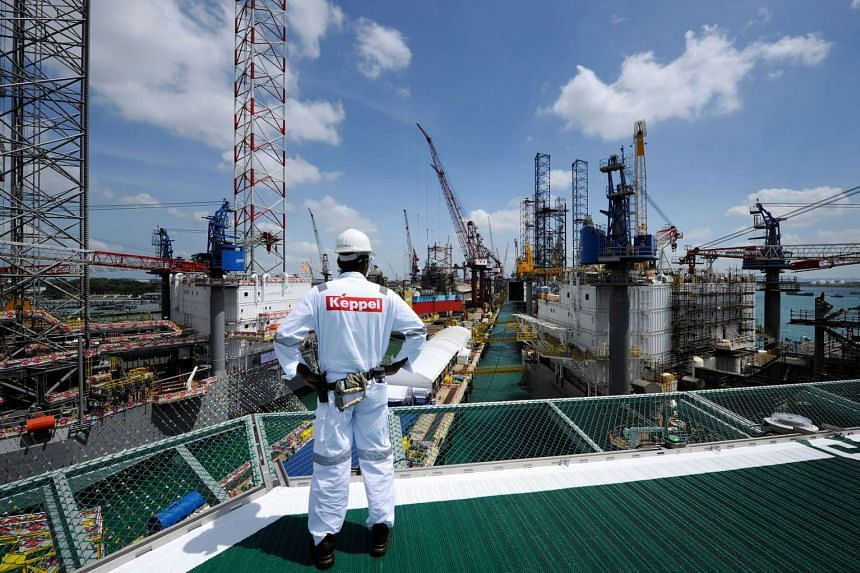 A Keppel Corp employee looks out towards jack up rigs.