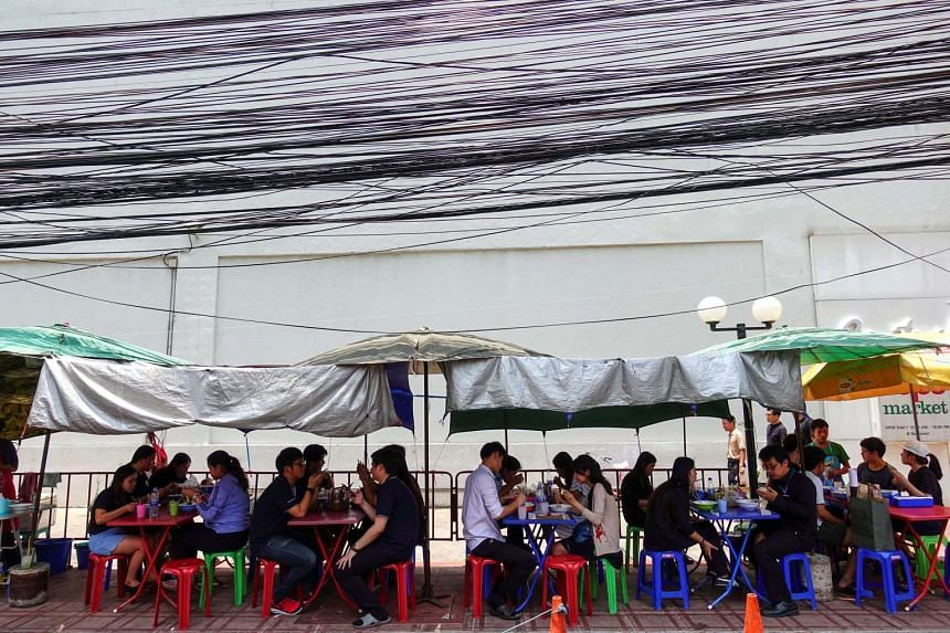 People eat their lunch at a street food shop in Bangkok, Thailand on April 20, 2017.