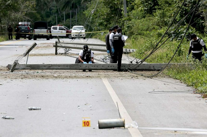 Thai forensic police officers inspect bomb damaged power poles at a blast scene in Pattani province, April 7, 2017.
