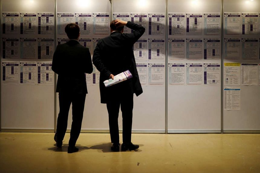 Men looking at recruiting information during a job fair in Seoul, South Korea.