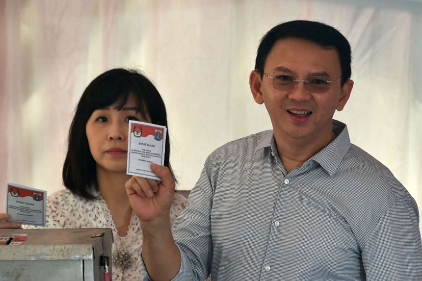 Basuki Tjahaja Purnama and his wife Veronica showing ballot papers at a polling station during the final-round of the Jakarta governor election in Jakarta on April 19, 2017.