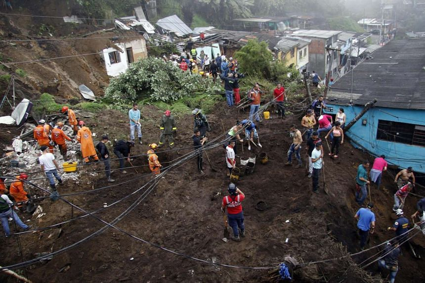 Rescue workers survey an area where a landslide destroyed several homes in Manizales, April 19, 2017.
