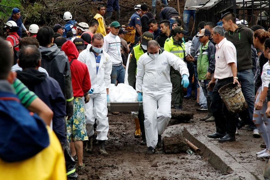 Rescue members recover a body from a house after the mudslides in Manizales, Colombia, April 19, 2017.