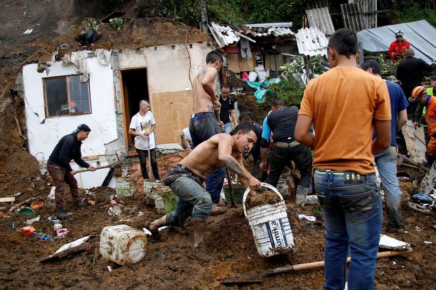 People look for bodies in a destroyed area after mudslides caused by heavy rains in Manizales, Colombia April 19, 2017.