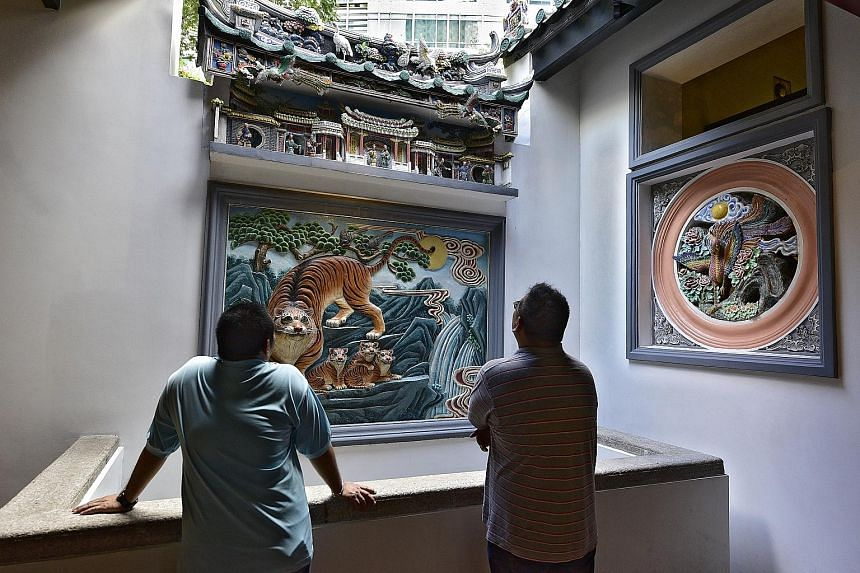 Left: A devotee lights joss sticks outside the right hall. Incense urns were moved outdoors to prevent smoke damage to historic carvings inside. Right: Temple caretakers admire a porcelain carving of a tiger and its cubs in the right hall, said to re