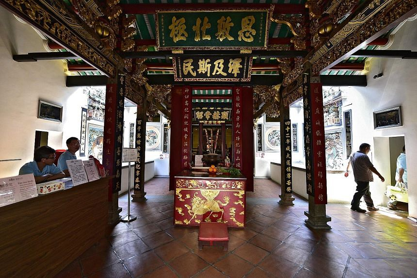 Left: Mr Ang Wenjie and Ms Chong Gaik See offering prayers to Yue Lao, the Chinese god of marriage, last November, as part of their marriage solemnisation ceremony. Right: The altar to the Jade Emperor in the temple, which also houses other famous de