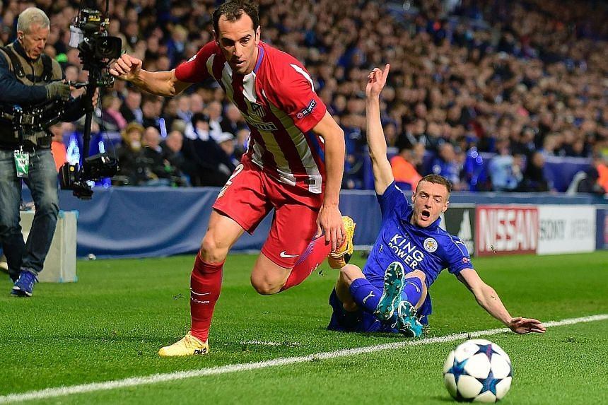 Leicester striker Jamie Vardy (right) reacts after challenging Atletico defender Diego Godin for the ball in their Champions League quarter-final second leg. Vardy equalised from close range in the second half.