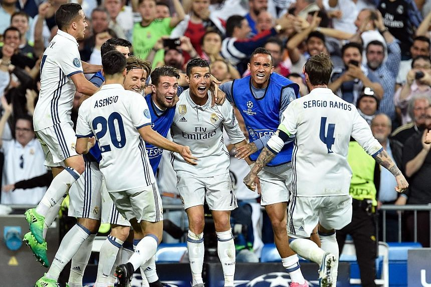 Real Madrid forward Cristiano Ronaldo celebrating his hat-trick against Bayern Munich with his team-mates. Ronaldo notched his 100th Champions League goal as holders Real rode their luck to seal progress to the semi finals.