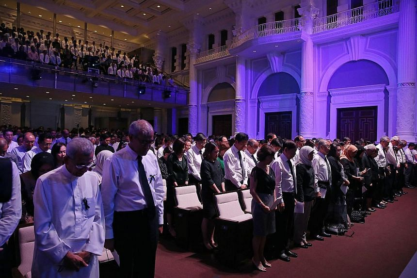 Attendees observing a minute of silence at the memorial service at Victoria Concert Hall yesterday.