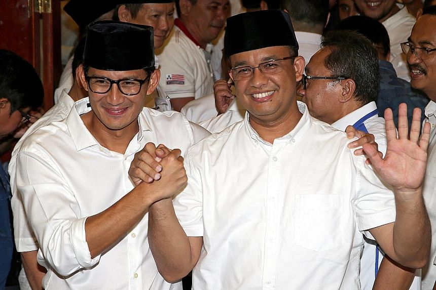 """Mr Anies Baswedan (right) and his running mate Sandiaga Uno celebrating as quick counts released after the Jakarta election yesterday indicated that they won almost 60 per cent of the vote. Mr Anies pledged: """"Our focus is social justice, ending inequ"""