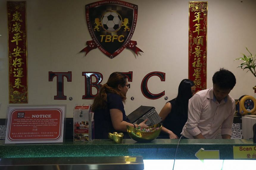 Investigators removing computers from the front desk of Tiong Bahru FC's clubhouse.