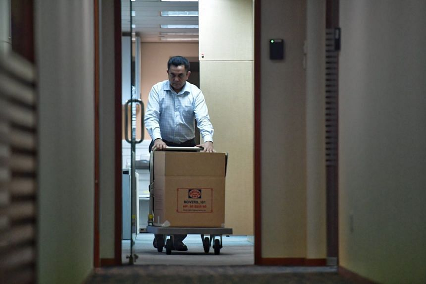 An officer removing a box of documents from FAS' Jalan Besar office.