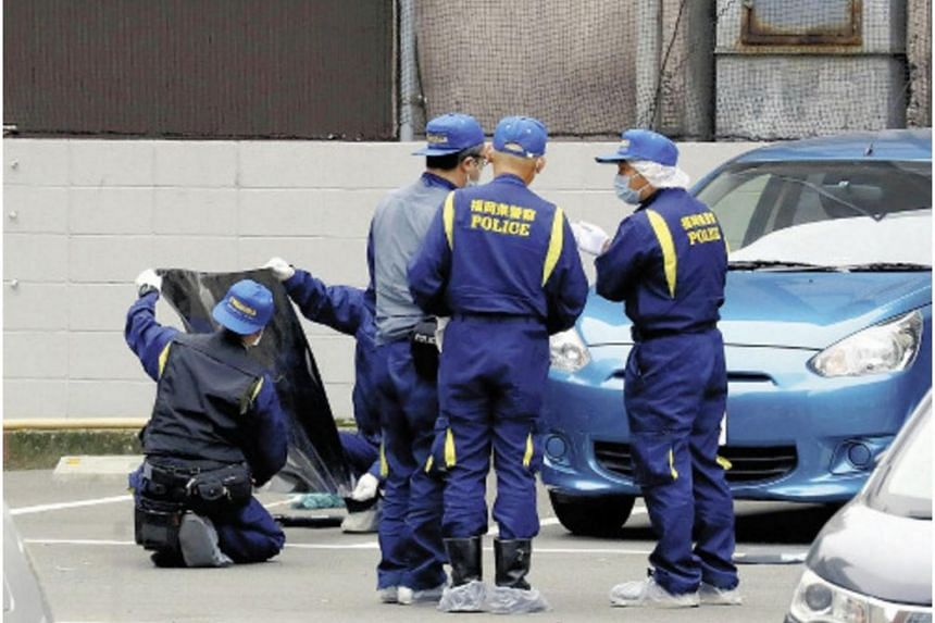 Japanese police officers at the scene of a robbery, where three robbers grabbed a case containing 380 million yen (S$4.9 million) from a businessman, in Fukuoka, on April 20, 2017.