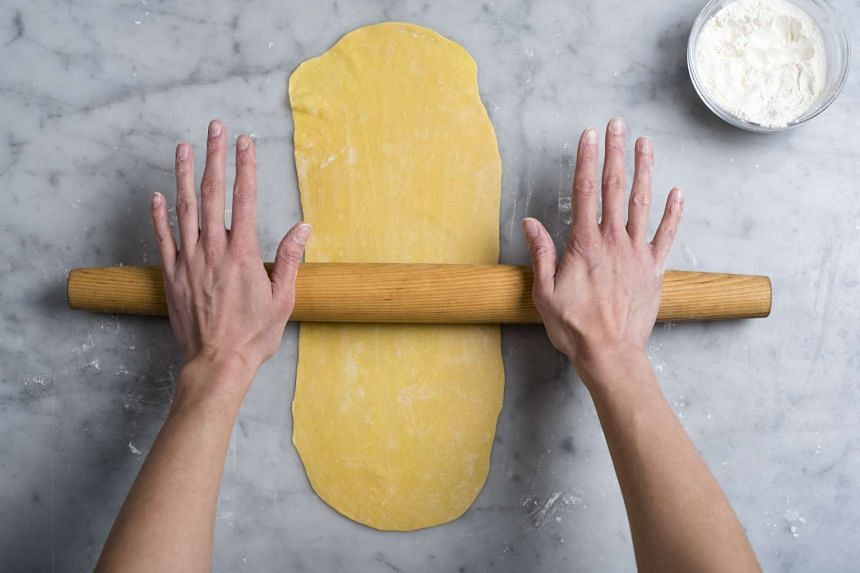 After folding rolled pasta dough into several layers, a knife is used to cut 1.25cm-wide noodles from basic pasta dough. PHOTO: NYTIMES
