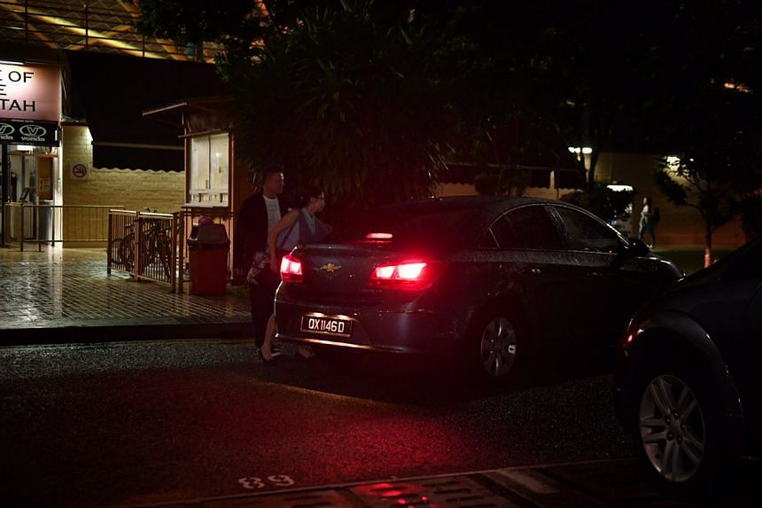 Hougang United general manager Matthew Tay being led away in a police car.