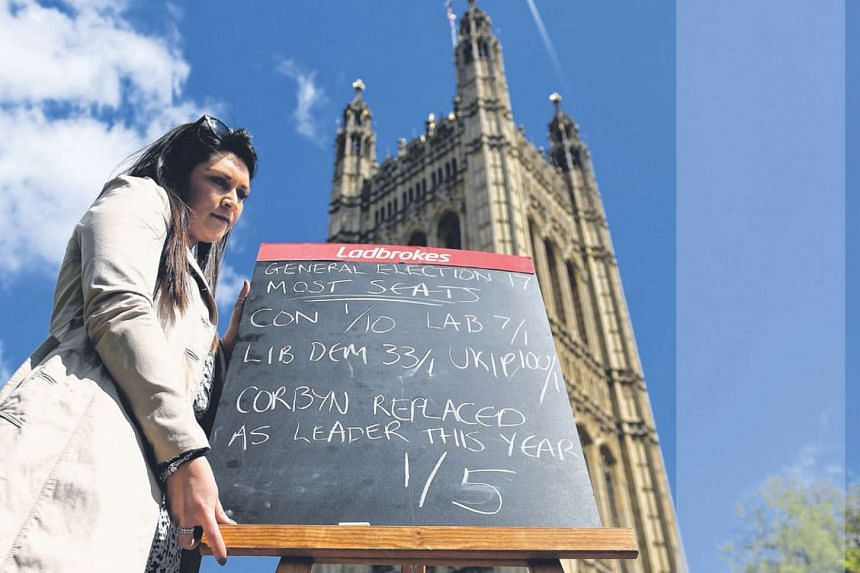 A Ladbrokes betting company staff member holding a sign showing the latest general election odds outside Parliament in London on Tuesday. The Prime Minister could see her majority increase by at least 100 seats at the polls as three MPs from the deeply d